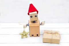 Robot con las manos en un casquillo del ` s del Año Nuevo y una caja de regalo Fotos de archivo