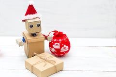 Robot con las manos en un sombrero de la Navidad y una caja de regalo Copie el espacio Fotos de archivo libres de regalías
