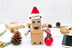 Robot con sus manos y en sombrero del ` s de Papá Noel en el fondo del Fotos de archivo