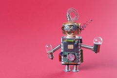 Robot concept retro style. Circuits socket chip toy mechanism, funny head, eyes glasses, light bulbs in hands. Copy Stock Images