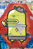 Robot Condom Graffiti. Kiev/Ukraine - February 24, 2015 - Graffiti of a yellow flying robot condom shaped with a hat on the head and a heart in the hand Royalty Free Stock Images