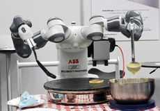 Robot cooking pancakes. STAVANGER, NORWAY - SEPTEMBER 01, 2017: The robot Yumi from RobotNorge cooks pancakes at Create, a festival for inventors and creators Royalty Free Stock Photography
