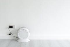 Robot de la limpieza que carga en la pared blanca Foto de archivo