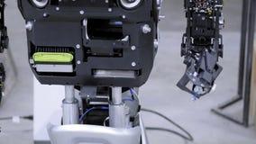 Robot desmontado en la producción El robot está listo para la asamblea, aumenta su mano Planta para la producción de robots almacen de metraje de vídeo