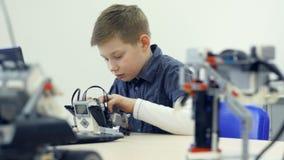 Robot di montaggio astuto del ragazzo di scuola 4K stock footage
