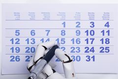 Robot die Datum op Kalender merken stock afbeelding