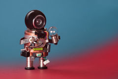 Robot electrician lamp bulb. Circuits socket chip toy cyborg, funny black helmet head. Copy space, blue red gradient. Background Stock Photo