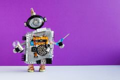 Robot electrician with light bulb screwdriver on violet wall gray floor background. copy space royalty free stock photos