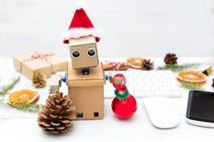 Robot en sombrero del ` s de Papá Noel en el fondo de la mesa y del Cristo Imágenes de archivo libres de regalías