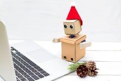 Robot en un sombrero del ` s del Año Nuevo que trabaja en un ordenador portátil Foto de archivo