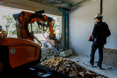 Robot Equipment is destroying the walls of the house Stock Images
