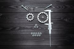 Robot face from gears tool and nuts on wooden background. Robot face from gears tool and nuts on dark wooden background royalty free stock photo