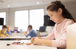 Robot felice della costruzione della ragazza alla scuola di robotica Fotografie Stock Libere da Diritti