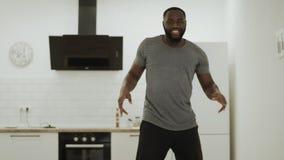Robot feliz del baile del hombre negro en la cocina abierta Individuo joven que se mueve lentamente en casa almacen de metraje de vídeo