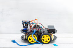 Robot on four wheels and a variety of cables with big blue wire Stock Images
