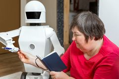 Robot friend is learning or teaching with an disabled woman, reaching her a pencil. Robot friend is learning or teaching with an mentally disabled woman stock photo