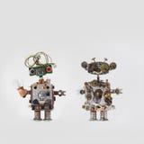 Robot futuristici su fondo grigio Giocattoli meccanici amichevoli con l'acconciatura del cavo elettrico, occhi rossi blu colorato Fotografia Stock