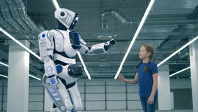 A robot and a girl touching hands, side view. School kid, education, science class concept. White android and girl touch hands stock footage