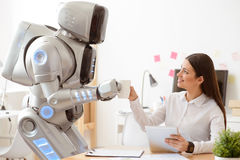 Robot giving cup of coffee to the girl. Pleasant thing for you. Robot bringing coffee to the woman who is sitting at the table and using tablet Royalty Free Stock Photo