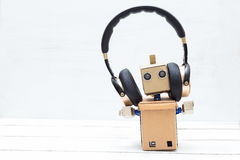 Robot in gold headphones on a light background Royalty Free Stock Photography