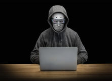 Robot hacker working with computer notebook Royalty Free Stock Photo