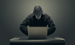 Robot hacker hiding in hood hacking computers Royalty Free Stock Photography