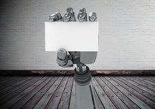 Robot hand holding a blank card in front of brick wall Stock Image