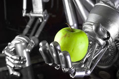 Robot hand holding green apple Royalty Free Stock Image
