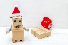 Robot with hands in a christmas hat and a gift box Royalty Free Stock Images