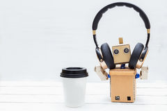 Robot with hands listening to music in golden headphones and dri. Nking coffee Stock Photography
