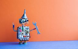 Robot handyman with hand wrench. Fixing maintenance concept. Creative design toy metal funnel hopper, cogs wheels gears. Metallic body. Orange wall, blue floor Royalty Free Stock Image