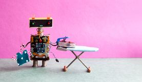 Robot hanger blouse, iron on the board. Pink wall green floor room interior. Creative design toys housework concept Royalty Free Stock Images