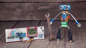 Robot hecho de partes de placas de circuito con la llave cerca de la eliminación de errores fotografía de archivo libre de regalías
