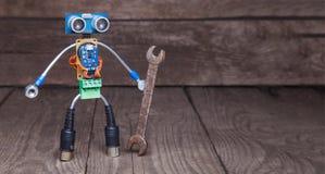 Robot hecho de partes de placas de circuito con la llave, en el backg de madera fotos de archivo libres de regalías