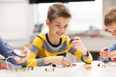 Robot heureux de bâtiment de garçon à l'école de robotique Image libre de droits