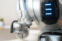 Robot holding glass of water Royalty Free Stock Images