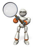 Robot holding a large magnifying glass Royalty Free Stock Photography