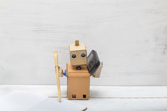 Robot holding a pen writing in diaries and talking on the phone. Stock Photo