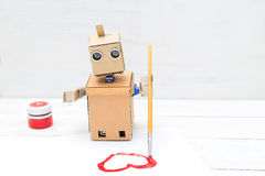 The robot holds a brush in his hand and draws it on a white shee. T of paper Stock Image
