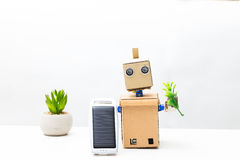 The robot holds a green plant and a solar battery in its hand. W Stock Images
