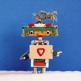 Robot holds greeting card love heart symbol. Valentines day romantic message for all lovers from robotic character. Robot holds greeting card love heart symbol stock photos