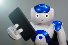 The robot holds the phone in his hand . A small robot with a human face and a humanoid body. Artificial intelligence-AI. Blue-white robot stock images