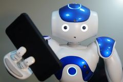 The robot holds the phone in his hand . A small robot with a human face and a humanoid body. Artificial intelligence-AI. Blue-white robot royalty free stock photography