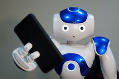 The robot holds the phone in his hand . A small robot with a human face and a humanoid body. Artificial intelligence-AI. Blue-white robot stock photo