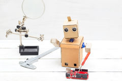 The robot holds a screwdriver and other tools in its hand Royalty Free Stock Image
