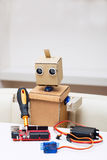 The robot holds a screwdriver and solder the red chip on the table Royalty Free Stock Photo