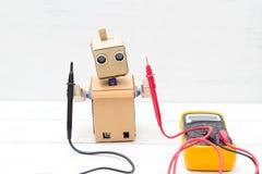 Robot holds voltmeter. horizontal. Robot holds voltmeter. Artificial Intelligencen stock image