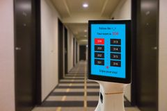 Robot in hotel concept, robotic butler help the customer to the room that booking, put the object, food, accessories inside it. Stock Image