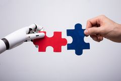Robot And Human Hand Holding Jigsaw Puzzle. Close-up Of Robot And Human Hand Holding Red And Blue Jigsaw Puzzle stock photo