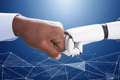 Robot And Human Hand Making Fist Bump. On Blue Digital Backdrop stock photography